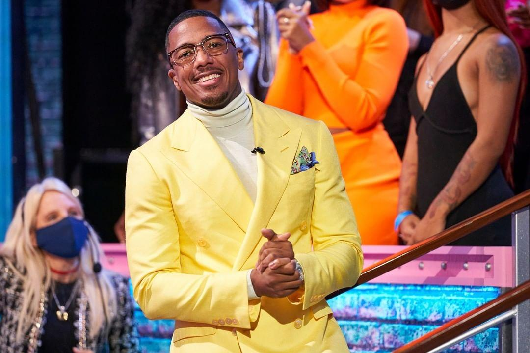 A photo showing Nick Cannon in a yellow color suit paired with a creme turtle neck sweatshirt.