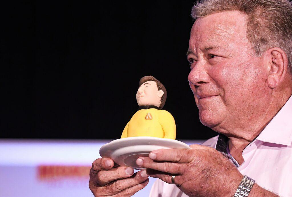 William Shatner holds a portion of a birthday cake presented to him at a Q